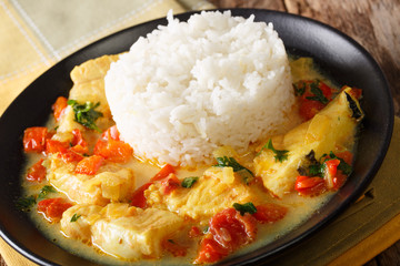 Stew fish with sauce of cilantro, onions, tomatoes, bell peppers and coconut milk with garnish of rice. Horizontal