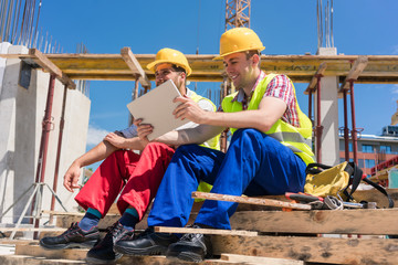 Side view of two workers, reading online information or watching a video on a tablet PC during break at work on the construction site of a contemporary building