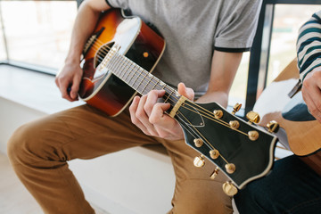 Learning to play the guitar. Extra-curricular lessons for adults. Music education. Masterclass playing the guitar