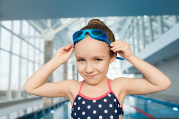 Cute little girl wearing swimsuit and goggles posing for photography while standing on edge of swimming pool, head and shoulders portrait shot