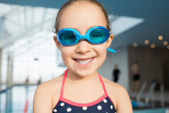 Head and shoulders portrait of cheerful little girl wearing swimsuit and goggles looking at camera with toothy smile while spending weekend in swimming pool, blurred background