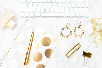 A feminine desk with gold objects. Flat lay