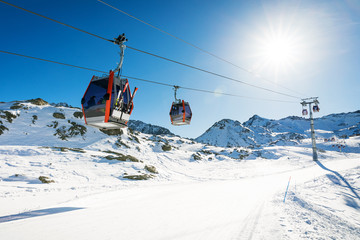 Türaufkleber Gondeln ski lift gondolas against blue sky over slope at ski resort on sunny winter day at Italy Alps