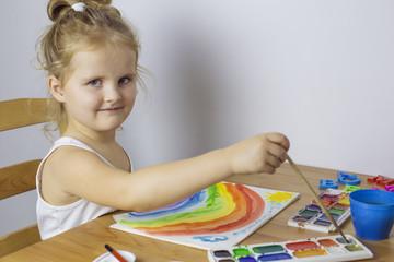 Cute girl draws a watercolor rainbow
