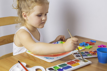 Happy young girl draws rainbow