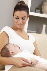 Young mother holding sleeping baby tenderly