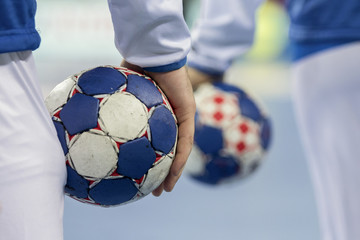 Handball players holding balls for handball