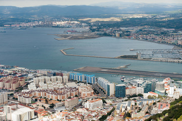 Aerial view on city and airport runway of Gibraltar and Spanish La Linea town on a background.