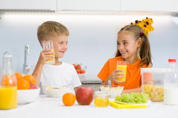 Happy children drink orange juice for breakfast