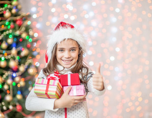 Happy little girl holding many gift boxes and showing thumbs up. Space for text
