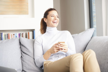 Online and mobile banking. A smiling brunette mature woman relaxing on her couch and text messaging on her cell phone.