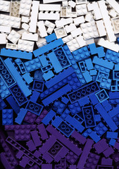 Lot of white, cyan, blue and purple Lego blocks background. Many arranged building bricks of bright marine colors. Educational toy for children