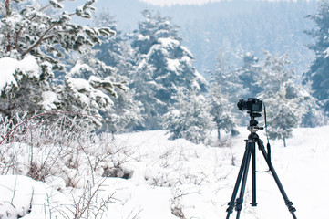 Winter landscape, camera on tripod in focus, big snow, cold weather.