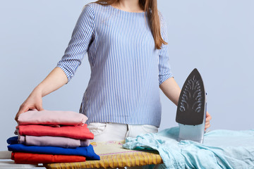 Unrecognizable female in blouse stands at iron board surrounded with pile of laundry, going to iron, isolated over blue background. Domestic work concept. Hard working housewife poses indoor.