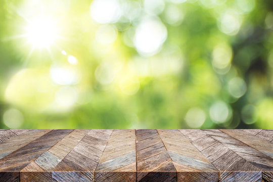 Empty old grunge wood plank table top with blur green tree in park bokeh sunlight,Mock up for display or montage of product,Banner or header for advertise on social media,Spring background.