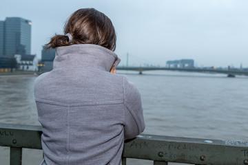 Junge Frau schaut auf den Rhein bei Köln