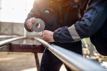Focus hand view of professional industrial workers in uniform bonding metal pipe with duct tape.