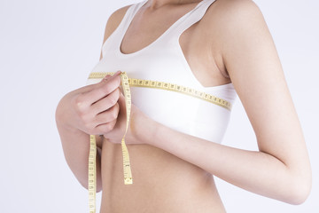 Young adult girl measuring her perfect breast - isolated on a white background