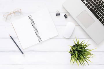 Minimal work space - Creative flat lay photo of workspace desk. Top view office desk with laptop, mock up notebooks and plant on white wooden background. Top view with copy space, flat lay photography
