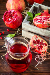Freshly squeezed pomegranate fruit juice and ripe pomegranate on a wooden table. The concept of nutrition for superfoods and health or detoxification.
