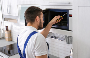 Young man repairing microwave oven in kitchen