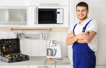 Young worker standing near microwave oven in kitchen