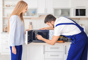 Housewife with worker near microwave oven in kitchen