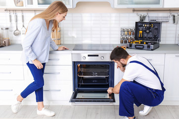 Housewife with worker near oven in kitchen