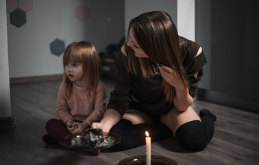Young beautiful mother guessing with a candle in the evening with a little daughter by the shadow on the wall
