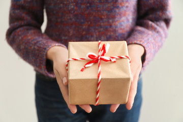 Woman holding parcel gift box on light background