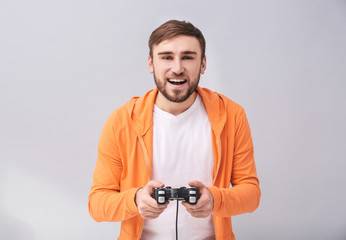 Happy man with video game controller on grey background