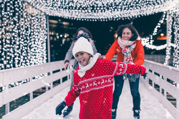 Mother with her daughter and friend enjoying in ice skating.