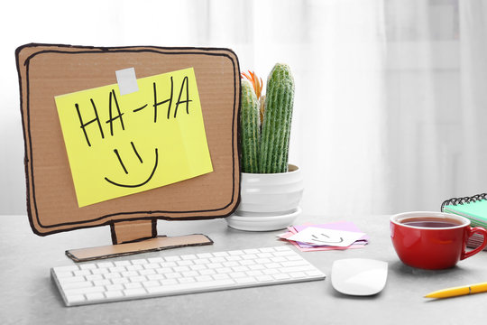 Computer with cardboard monitor on office table. April fool's day celebration