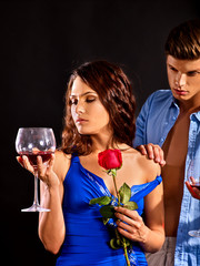 Couple drink red wine glass together. Woman hold rose flower. Man undresses his beloved woman. Relations without obligations. Acquaintance in a night club.