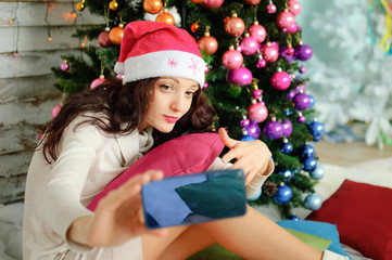 Christmas Portrait of Pretty Woman Wearing Pink Santa Hat and Taking Selfie on Blue Mobile Phone on Xmas Tree Background with Colorful Glass Balls.