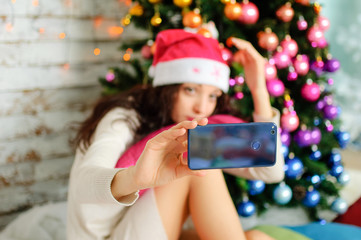 Portrait of Beautiful Brunette with Long Dark Hair in Pink Santa Hat Photographing Herself Using Gadget near Christmas Tree with Colorful Glass Balls.