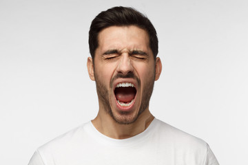 Closeup portrait of screaming with closed eyes crazy young man isolated on gray background