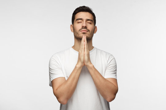 Picture of young man dressed casually isolated on grey background, having put hands together in prayer or meditation, looking relaxed and calm, dreaming