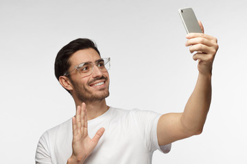 Photo of handsome man in white tshirt isolated on grey background, stretching arm with smartphone to say hi to friends in video chat