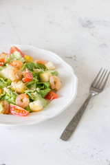 Caesar salad with shrimps on a white background