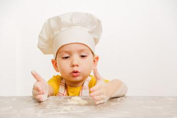 Details of children's hands kneading dough. Cheerful cook child boy in a cap prepares burritos