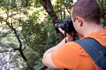 Professional male photographer in forest / Guys tourist in nature photography forest natural environment, enjoying beautiful day. Man photographer taking photo of nature. Traveling, adventure concept.