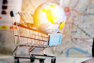 Global map ball America in small shopping cart on tablet. Road map background. Concepts online shopping consumers can buy insurance directly from anywhere, world wide. Taking few clicks via Internet