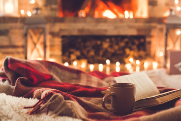 One cup and a book near the fireplace winter concept