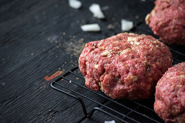 raw hamburger patties with onions and herbs