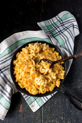 top view gourmet baked macaroni and cheese noodles in rustic cast iron dish