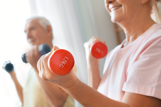 Senior couple exercise together at home health care dumbbells close-up