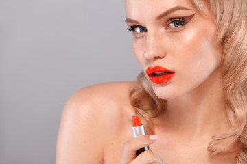 Close up portrait of attractive girl rouging her lips. She is holding red lipstick in the mouse. Isolated on gray background with copy space