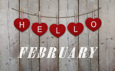 Hello february written on hangingred hearts and weathered wooden background