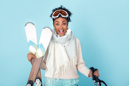 Young african woman isolated on blue wall studio winter sport skiing